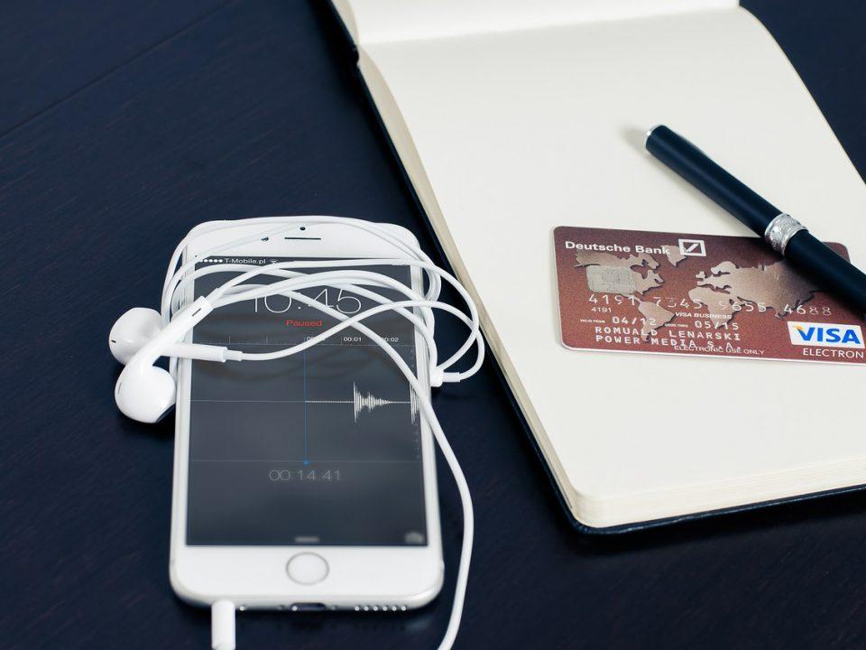 Un Iphone, une carte bancaire et un stylo se trouvent sur un bloc note