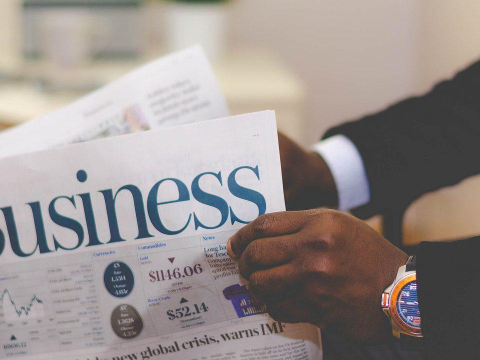 Une personne lit un journal dont le sujet est le business