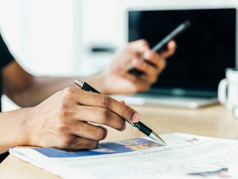 Une personne lit un journal en tenant un stylo à la main