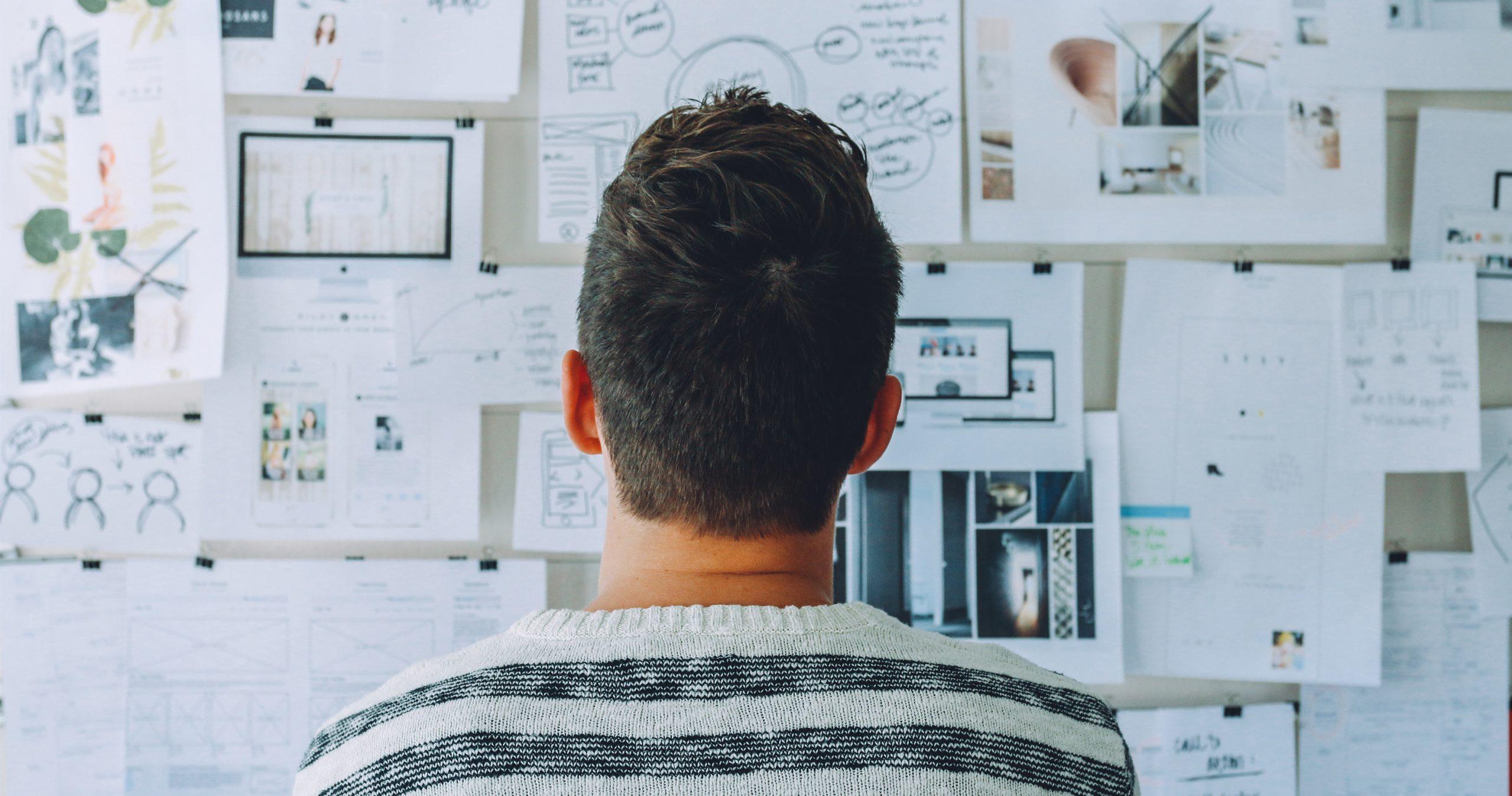 Une personne réfléchissant devant un mur couvert d'informations