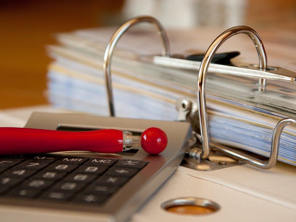 Un stylo et une calculatrice sont posés sur un dossier de financement